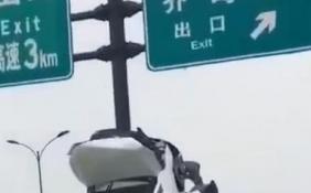 杭州轿车开上天了 车子几乎垂直靠在交通标志杆上